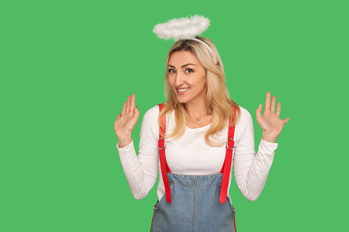 istock Not me! Portrait of lovely adult woman with halo above head raising hands in bewilderment, denying guilt 1222554212