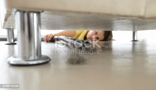 Young woman reaching under a sofa to get at some dust