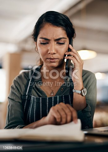 Shot of a young woman using a smartphone while working in a cafe