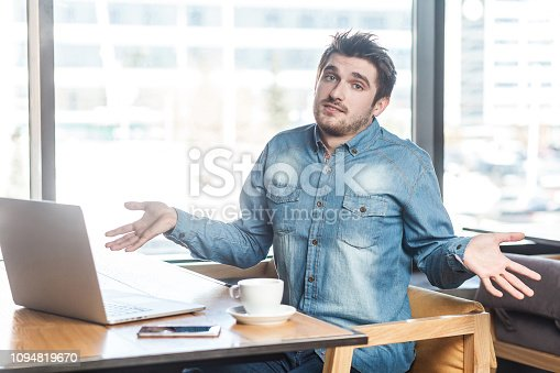 istock Not sure! Portrait of confused handsome bearded young freelancer in blue jeans shirt are sitting in cafe and working on laptop with raised arms and puzzled face, looking at camera. 1094819670