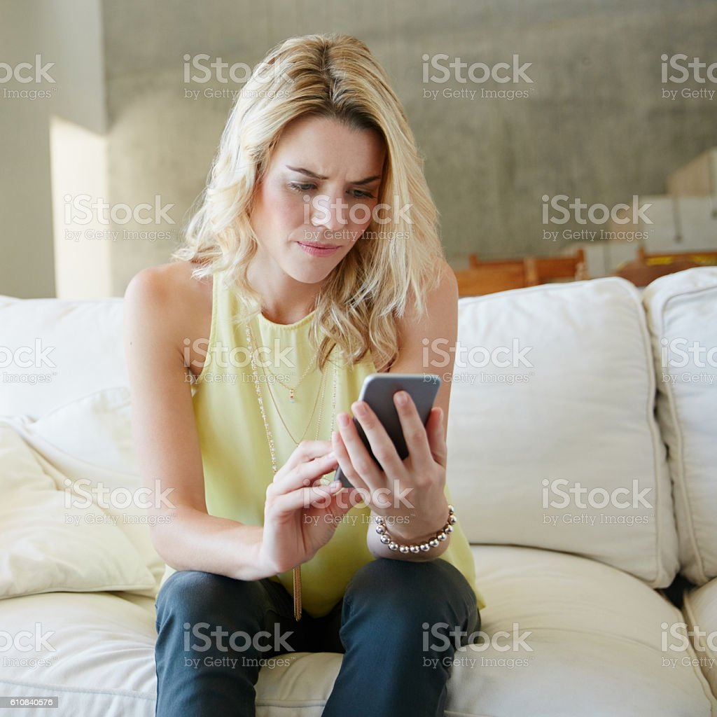 Not the news she was hoping for Shot of a stressed young woman looking at her phone at home 20-29 Years Stock Photo