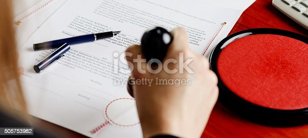 854317150istockphoto Notary public stamping document. 505753982