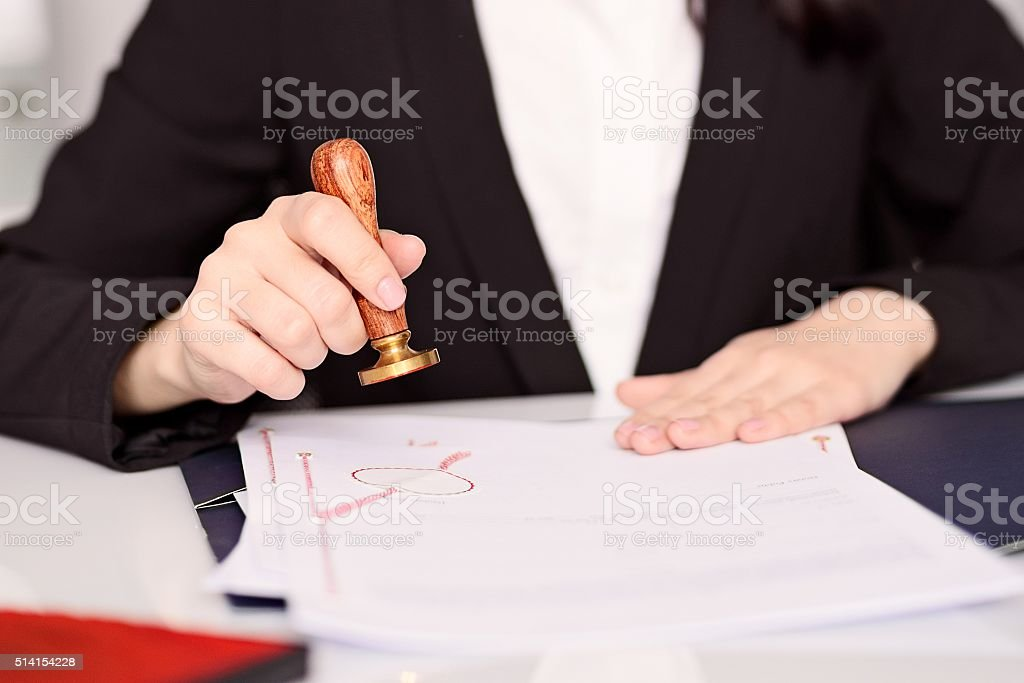 Notary Public woman hands stamping notary act . stock photo