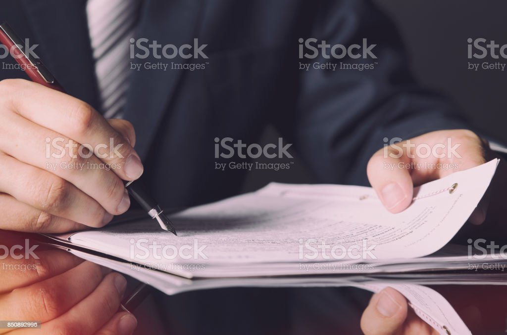 Notary signing a contract with fountain pen in dark room concept – zdjęcie