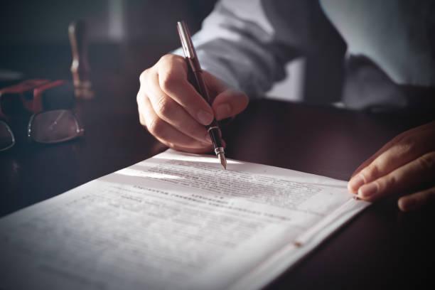 notaris ondertekening van een contract met vulpen - notaris stockfoto's en -beelden