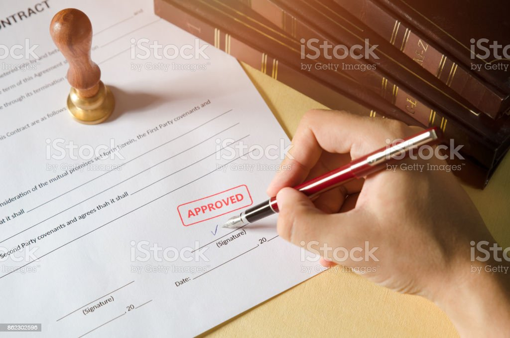 Notary signing a contract with fountain pen stock photo