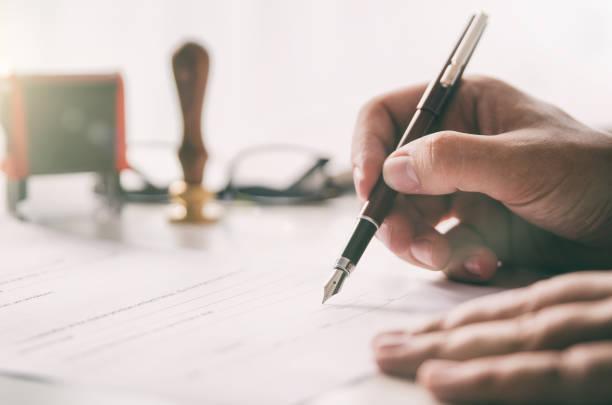 нотариус подписывает юридический договор. бизнесмен, работающий в офисе - письмо документ стоковые фото и изображения