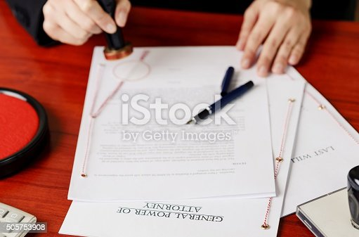 854317150istockphoto Notary's public hands stamping power of attorney. 505753908