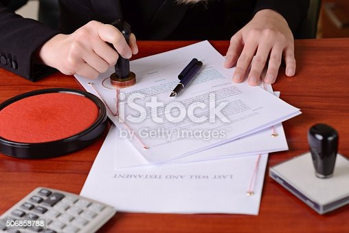 istock Notary's public hands stamping the testament and last will 506858788