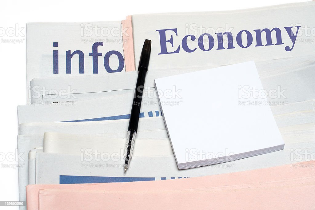 Note and pen, over stacked economy newspapers on white backgroun royalty-free stock photo