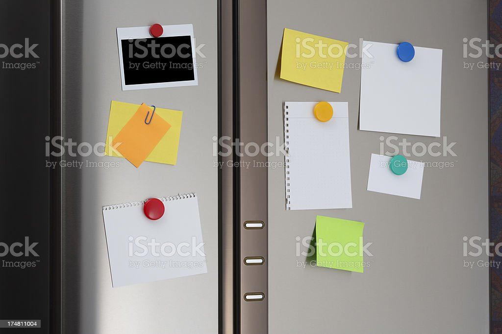 Note and polaroid on Refrigerator Door stock photo