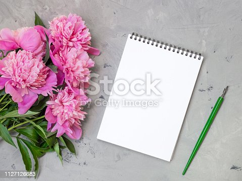 1147767708 istock photo note book with pink peonies on a stone background, copy space for your text top view and flat lay style. 1127126683