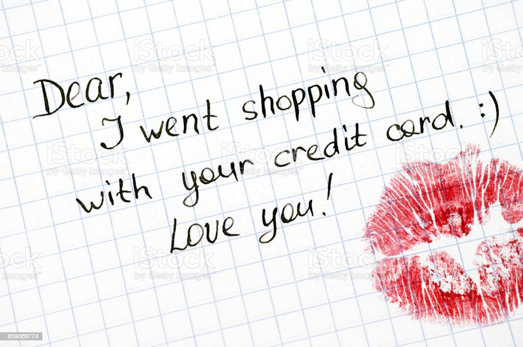 Note - Dear, I went shopping with your credit card. Love you! with kiss on paper. stock photo