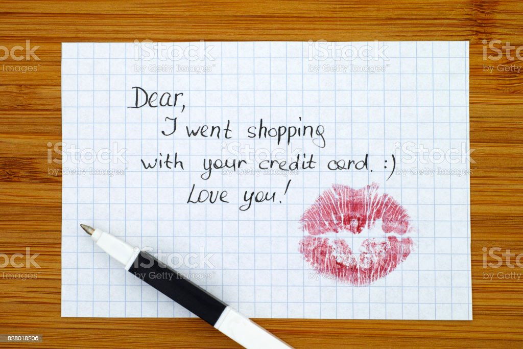 Note - Dear, I went shopping with  your credit card. Love you! with kiss and pen. stock photo