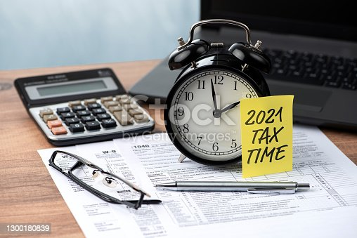 2021 TAX TIME note is on the alarm clock. Tax and business concepts