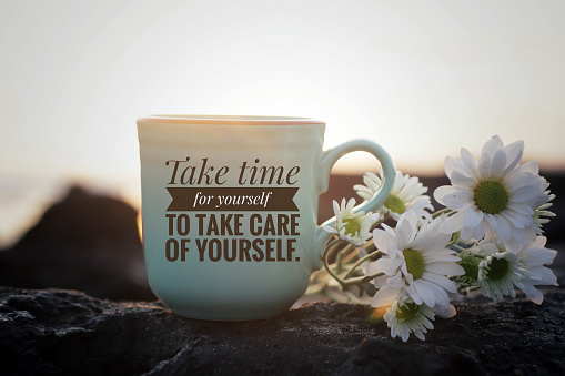 Self love inspirational motivational words - Take time for yourself to take care of yourself. Written on a cup of morning tea or coffee with white daisy flowers on sea rock in the beach on background of sunset sunrise light.