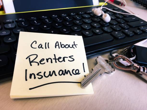 Note on desk keyboard to call about renters insurance stock photo