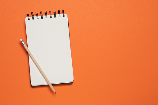 Spiral notebook and pencil on orange background