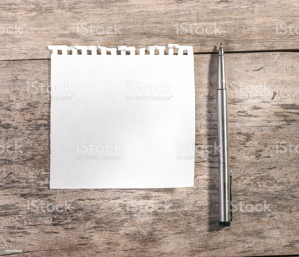 Note pad  on an old grungy wooden board or surface. stock photo