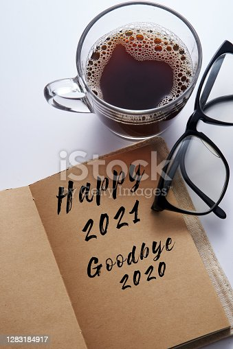 note pad written happy 2021 goodbye 2020 with cup of coffee