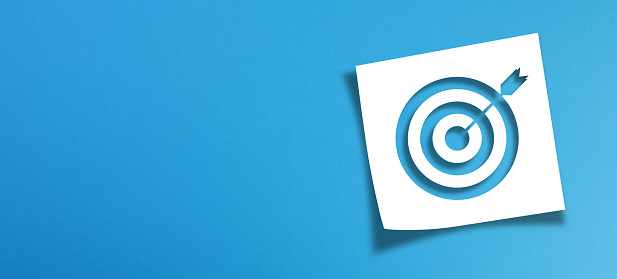 Note paper and target sign with copy space on panoramic blue background