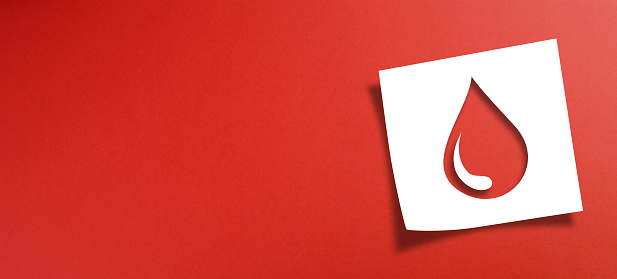 Note paper with blood donation concept on red background
