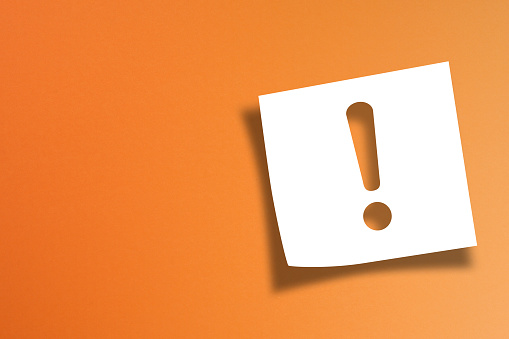 istock Note paper with exclamation mark on orange background 1186110995