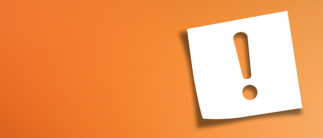 istock Note paper with exclamation mark on panoramic orange background 1203903460
