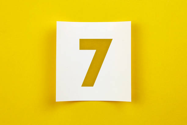 Note paper with number seven on it. White note paper on yellow background number 7 stock pictures, royalty-free photos & images