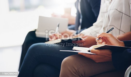 Cropped shot of unrecognizable businesspeople sitting and writing notes in a book while in the office during the day