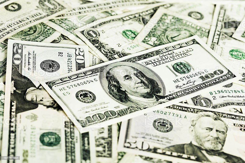 $100 note tops a pile of money royalty-free stock photo