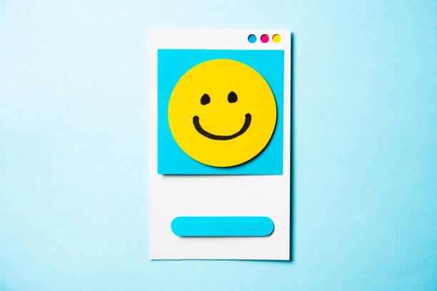 beachten sie mit glückliches gesicht und papier smartphone-konzept auf blauem hintergrund. social media und digitale marketing-konzept. - popup cards stock-fotos und bilder