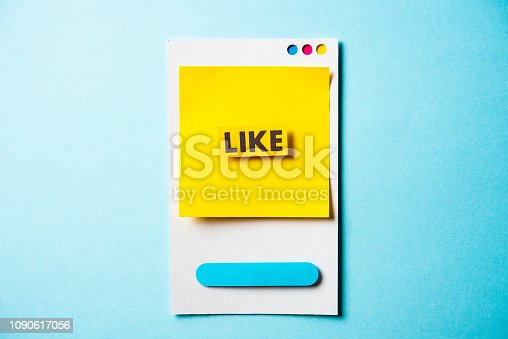 Note with Like word and paper smart phone concept on blue background. Social media and digital marketing concept.