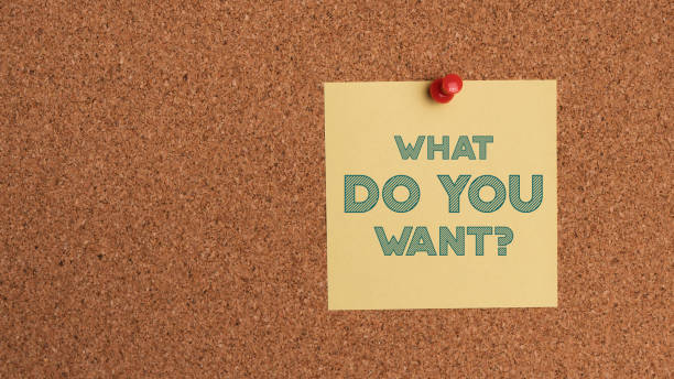 Note with text question on corkboard. Business concept, needs, want, strategy, plan, planning. stock photo
