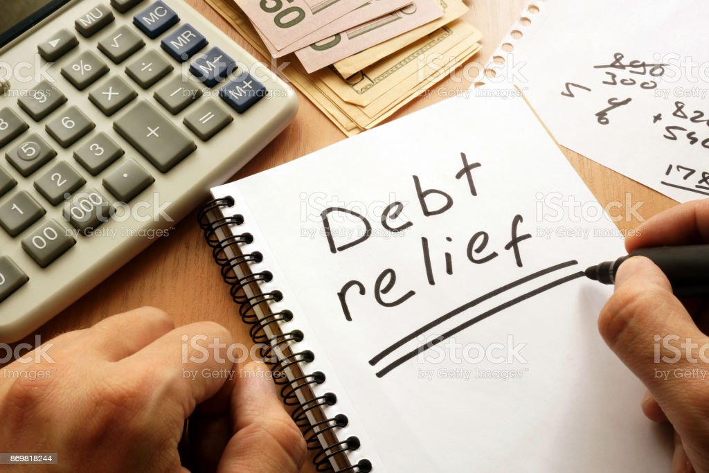 Note with words debt relief on a table. stock photo