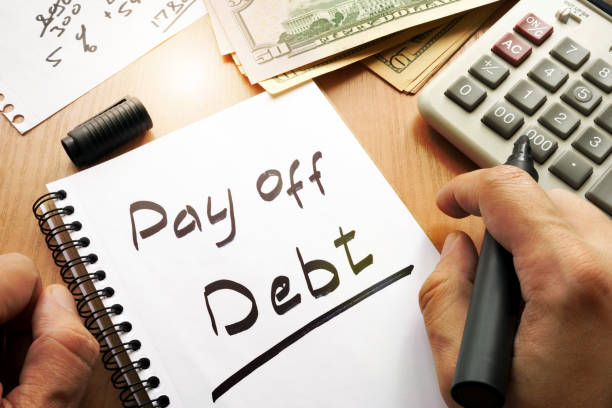 Note with words pay off debt concept. stock photo