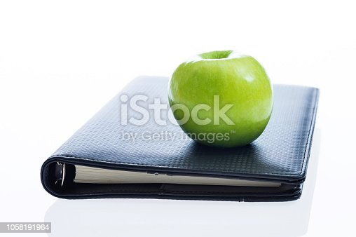 Notebook and an apple on white background.