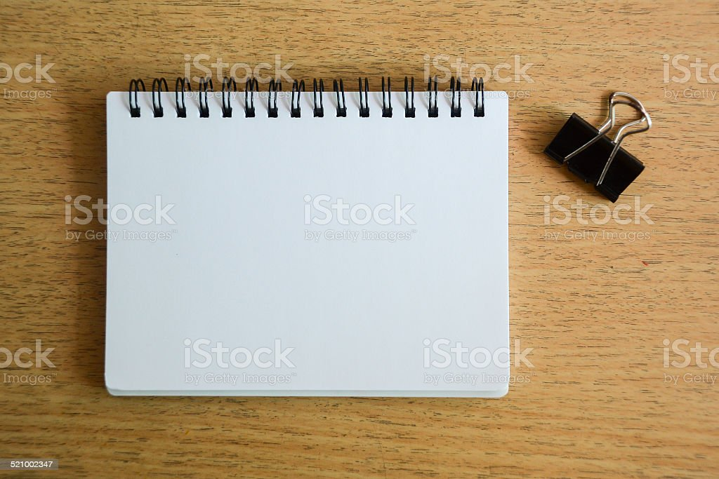notebook and black paper clip on wood desk stock photo