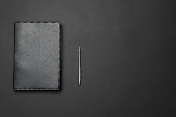 Cuaderno y pluma en el escritorio - foto de stock