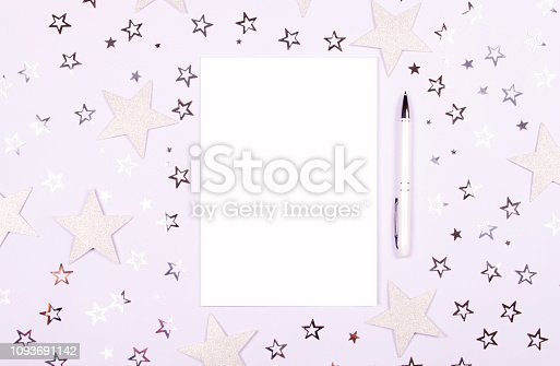 Notebook with blank page and pen on white table decorated with shiny and glitter star confetti. Bright and festive backdrop. Minimalist greeting concept. Top view with copy space.