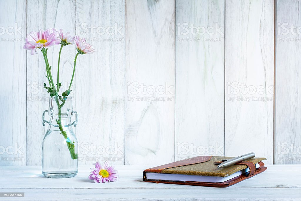 notebook and pen with flower on white wooden table stock photo