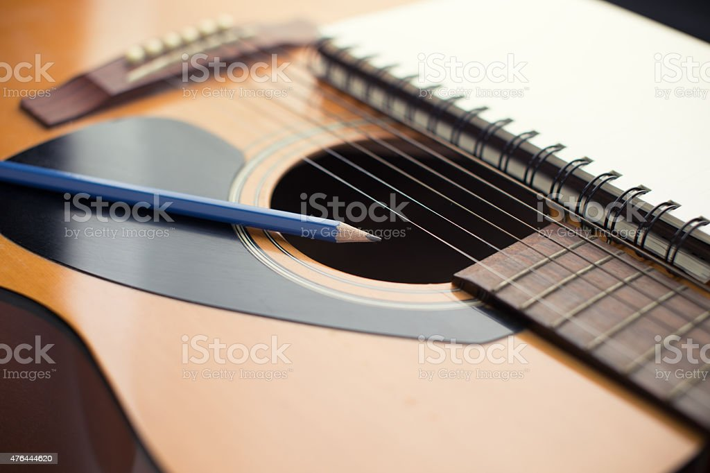 Notebook and pencil on guitar stock photo