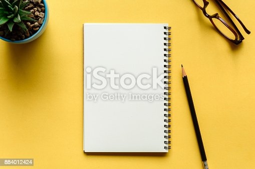 istock notebook and pencil on yellow desk 884012424