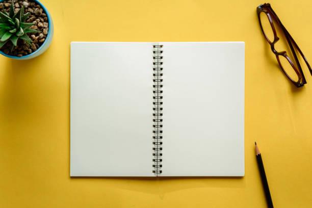 cahier et crayon sur bureau jaune - Photo