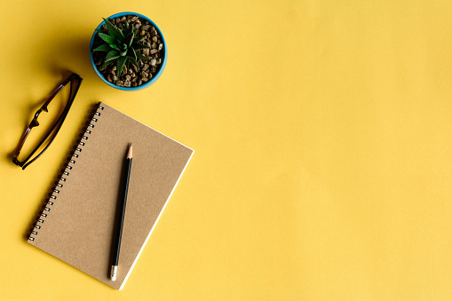notebook and pencil on yellow desk