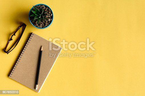 istock notebook and pencil on yellow desk 907650310