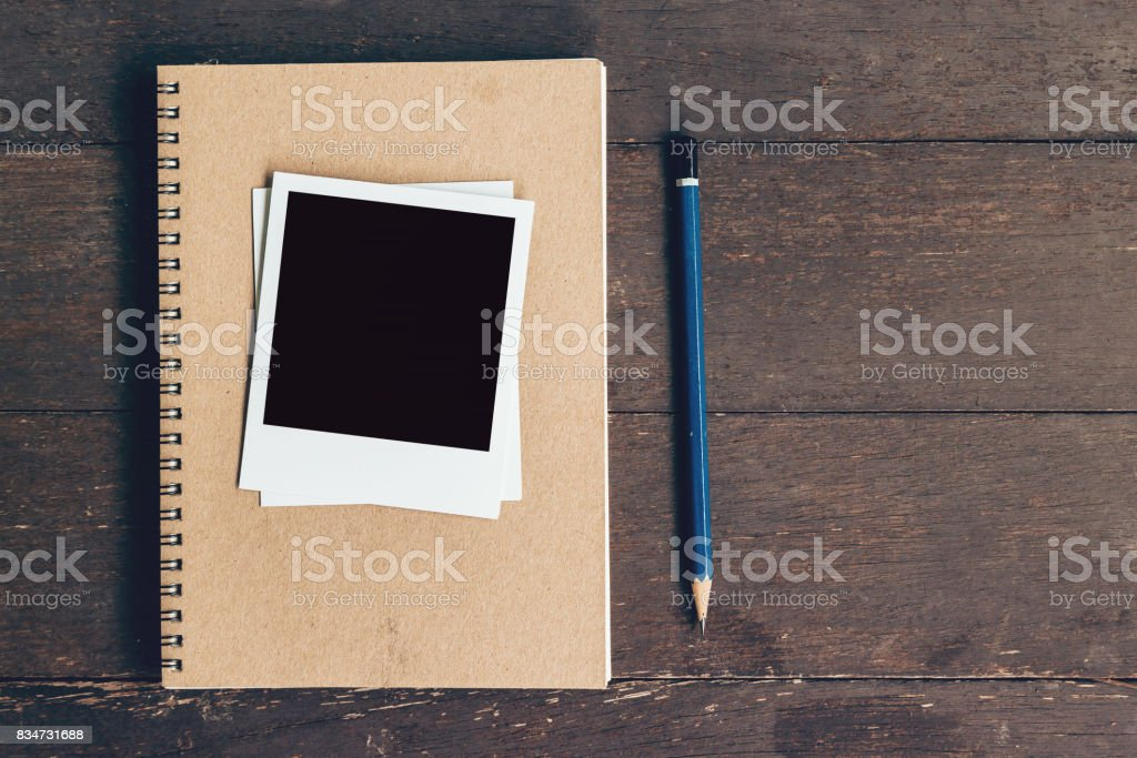 notebook and pencil with frame photo on wood table background with space stock photo
