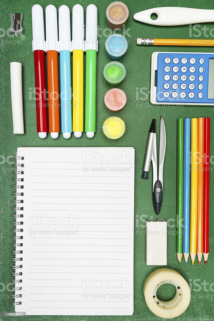 Notebook and school supplies on a chalkboard royalty-free stock photo