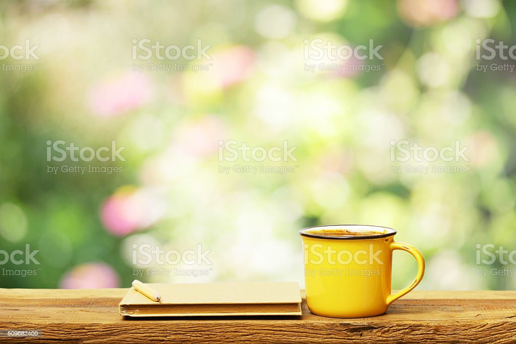 Notebook and yellow cup on wooden table stock photo