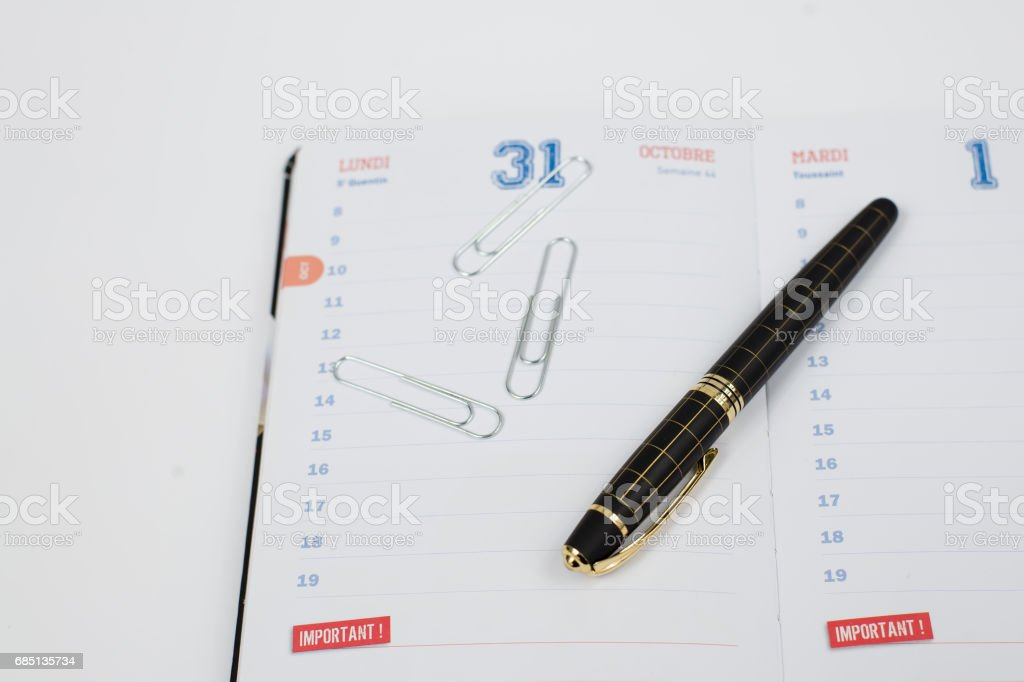 Notebook calendar, pen and three paper clips. Selected fucus. royalty-free stock photo